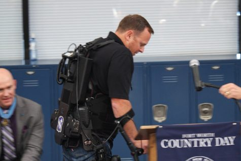 Gary Linfoot walks to the podium with the help of an bionic exoskeleton. He was paralyzed after a helicopter accident while serving in Afghanistan.